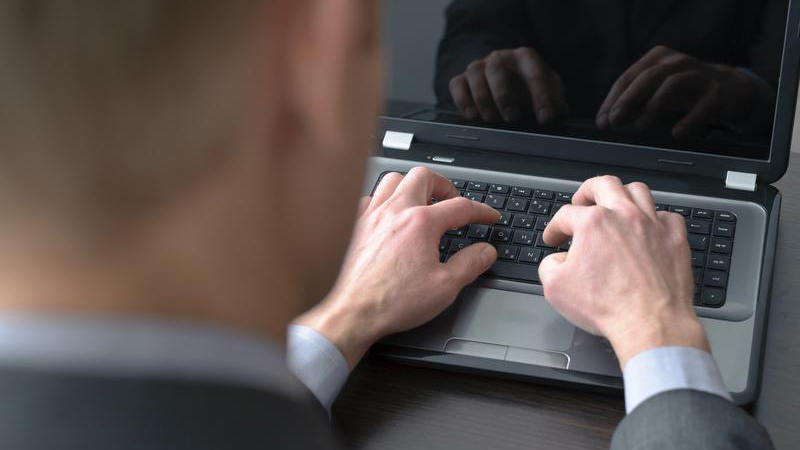 Man's hands on laptop keyboard.