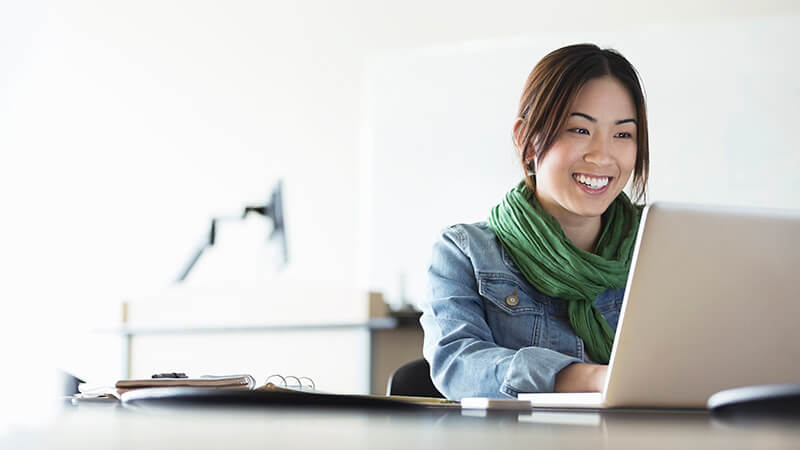 Woman smiling using her laptop in an office.