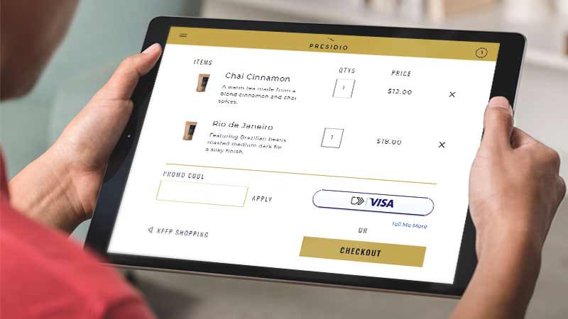 A woman holds a tablet that displays the new checkout experience.